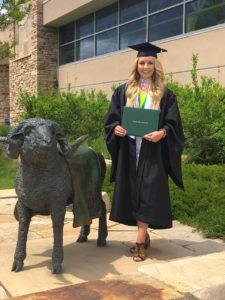 Hailey Fredricksen poses with a bronze ram near Moby on her graduation day in May, 2019.