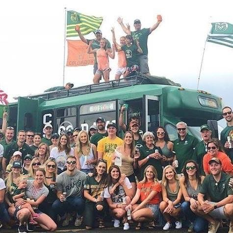 A group of tailgaters poses in front of the Caldwell's bus