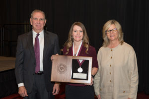 Rapp displaying her teaching award with Texas A&M President Michael K. Young, left, and Director of the Center for Teaching Excellence Debra Fowler, right.