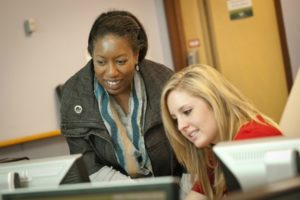 Alumna teaching student at a computer
