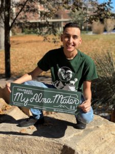 """Graduating CSU student with sign saying, """"My Alma Mater"""""""