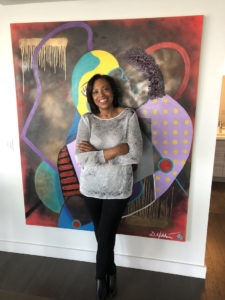 Charilynn in front of one of artist Daniel Hibbert's paintings