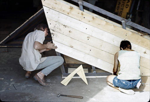 Two artists working on a wooden sculpture