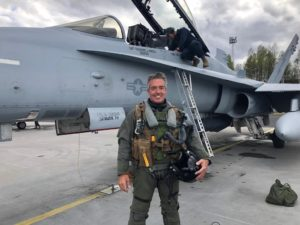 Reporter standing next to F-18 fighter jet